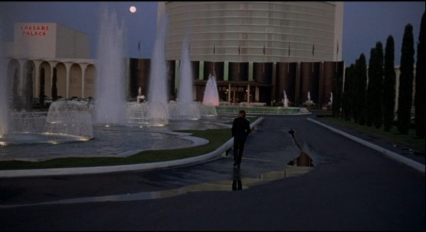 Robert Drivas walks by the fountains at dusk/dawn, right before a crucial part of the scattered plot unfolds.