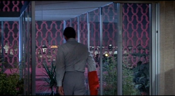 One of my favourite shots of the film: the owner's penthouse is connected to his executive office via a glass skywalk concealed by the stone latticework. Only in the 60s!