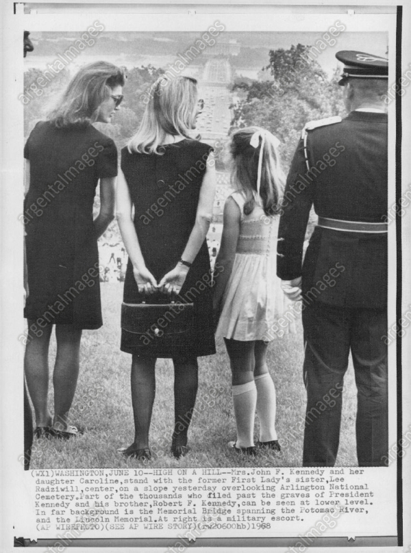 "Provided caption: ""High On A Hill -- Mrs. John F, Kennedy and her daughter Caroline, stand with the former First Lady's sister, Lee Radziwill, center, on a slope yesterday overlooking Arlington National Cemetery. Part of the thousands who filed past the graves of President Kennedy and his brother, Robert F. Kennedy, can be seen at lower level. In far background is the Memorial Bridge spanning the Potomac River, and the Lincoln Memorial. At right is a military escort."""
